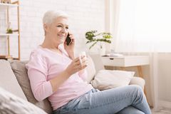 Cheerful senior lady having phone call on her smartphone stock image