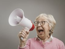 Cheerful senior lady shouting into a megaphone. Cheerful senior woman shouting into a megaphone, communication and advertising concept royalty free stock photo