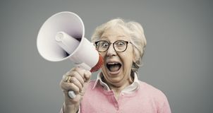 Cheerful senior lady shouting into a megaphone. Cheerful senior woman shouting into a megaphone, communication and advertising concept stock photo