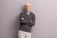 Cheerful senior leaning against a gray wall Royalty Free Stock Photo