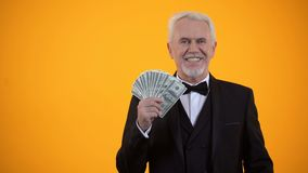 Cheerful senior male with dollars showing hey you gesture, successful investment stock video