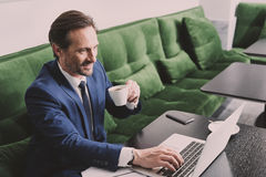 Cheerful senior male manager drinking beverage in cafe Stock Photography