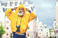 Cheerful senior male tourist walking in town Stock Photo