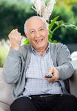 Cheerful Senior Man Clenching Fist While Using Royalty Free Stock Photo