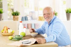 Cheerful senior man having breakfast Stock Photo