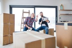 A senior man helping his son with furnishing new house, a new home concept. A cheerful senior men helping his mature son with furnishing new house, a new home stock photos