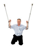 Cheerful senior man holding crutches upwards. Seated on floor, studio shot Royalty Free Stock Images