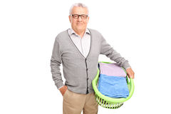 Cheerful senior man holding a laundry basket Royalty Free Stock Photo