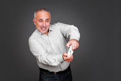 Cheerful senior man with joypad. Over grey background Royalty Free Stock Images