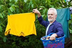 Cheerful senior man with laundry basket outdoor Royalty Free Stock Photos