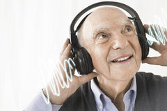 Cheerful senior man listening music through headphones against white background Royalty Free Stock Image