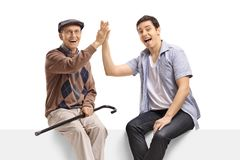 Cheerful senior man and a young man high-fiving each other on a panel and looking at the camera. Cheerful senior men and a young men high-fiving each other on a royalty free stock image