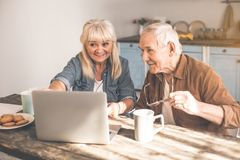 Cheerful senior married couple using computer in cook room. Excited mature pensioners watching video on laptop in kitchen. They are drinking tea with cookies and Royalty Free Stock Photos