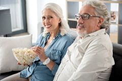 Cheerful senior married couple watching television at home Stock Photos