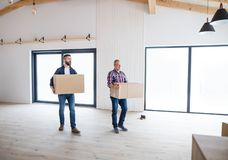 A senior man helping his son with furnishing new house, a new home concept. A cheerful senior men helping his mature son with furnishing new house, a new home royalty free stock photos