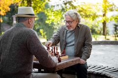 Cheerful senior men playing chess together outdoor royalty free stock photos