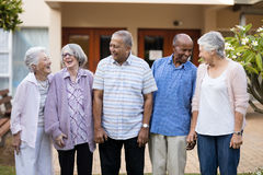 Cheerful senior men and women at nursing home. Cheerful senior men and women standing at retirement nursing home Royalty Free Stock Image