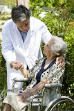 Cheerful senior patient in wheelchair with a friendly caregiver outside Royalty Free Stock Photography