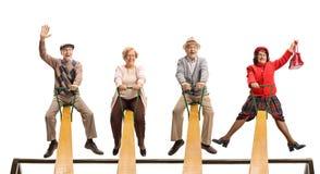 Cheerful senior people having fun on a seesaw stock photography