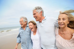 Cheerful senior people walking on the beach Royalty Free Stock Photo