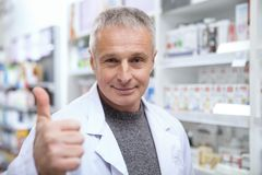 Mature pharmacist helping his female customer royalty free stock image