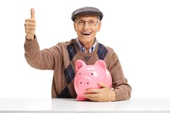 Cheerful senior with piggybank making a thumb up sign. Cheerful senior with a piggybank seated at a table making a thumb up sign isolated on white background Stock Photo