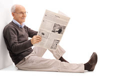 Cheerful senior reading a newspaper. Cheerful senior gentleman reading a newspaper seated on the floor isolated on white background Stock Photography