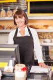 Cheerful senior saleswoman is selling bakery Royalty Free Stock Photos