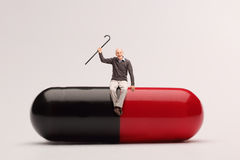 Cheerful senior sitting on a giant pill Stock Image