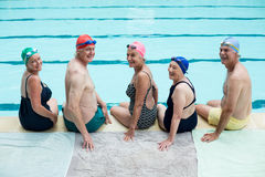 Cheerful senior swimmers sitting at poolside. Portrait of cheerful senior swimmers sitting at poolside Stock Image