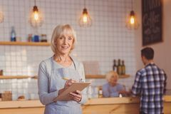 Cheerful senior waitress making a list of customers orders. Enjoying work. Pleasant upbeat elderly waitress making a list of her customers orders and smiling at royalty free stock images