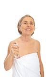 Cheerful senior woman applying perfume Stock Photo