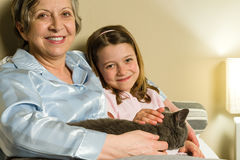Cheerful senior woman with granddaughter and cat Royalty Free Stock Photography