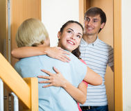 Cheerful senior woman greeting adult children coming with visit. Happy mature mother meets son with his wife at doorway stock photography