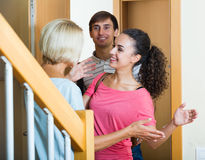 Cheerful senior woman greeting adult children coming with visit. Happy mature mother meets son with his wife at doorway royalty free stock photos