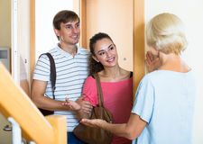 Cheerful senior woman greeting adult children coming with visit. Happy mature mother meets son with his wife at doorway stock photos