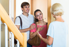 Cheerful senior woman greeting adult children coming with visit. Happy mature mother meets son with his wife at doorway royalty free stock images