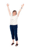 Cheerful senior woman lifting her arms up Stock Photo