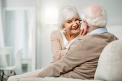 Cheerful senior woman looking at her husbands face. Happy family. Cheerful nice senior women looking at her husbands face while smiling to him Stock Photos