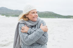 Cheerful senior woman shivering at beach Royalty Free Stock Image