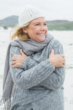 Cheerful senior woman shivering at beach Royalty Free Stock Photography