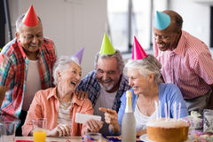 Cheerful senior woman showing mobile phone to friends in party. Cheerful senior women showing mobile phone to friends during birthday party at nursing home stock image