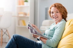Cheerful senior woman sitting on the couch. At home is the best. Joyful smiling senior woman sitting on the couch and reading magazine while resting Royalty Free Stock Photography
