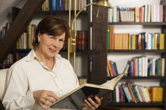 Cheerful senior woman sitting and reading a book Stock Image
