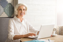 Cheerful senior woman sitting at the table. Never late to learn. Positive delighted senior woman sitting at the table and using laptop while expressing gladness royalty free stock photos