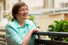 Cheerful senior woman sitting on terrace Stock Photography