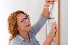 Cheerful senior woman sticking calendar to the board Stock Photo