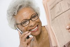 Cheerful Senior Woman Studying Stocks And Shares In Newspaper. Happy African American senior women reading stocks and shares in newspaper while using cell phone stock photography