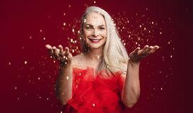Cheerful senior woman throwing sparkles stock images