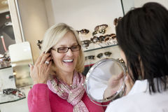Cheerful senior woman trying on glasses while optician holding mirror Stock Photography